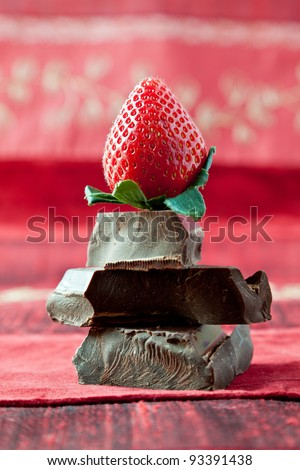 Strawberry on top of pile of gourmet thick dark chocolate bar chunks. Red textured background.