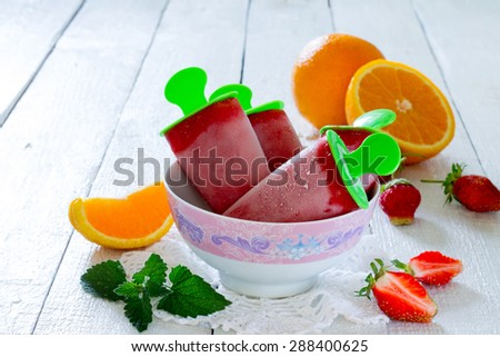 Strawberry-orange ice cream popsicle - stock photo