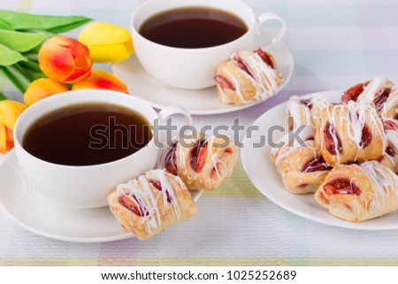 Strawberry pastries and coffee with colorful tulips on a table
