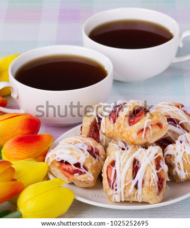 Strawberry pastries with coffee and colorful tulips