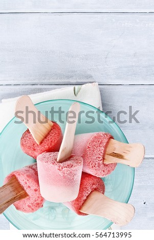 Strawberry popsicles made from strawberries and yogurt over a wood table top. Shot from overhead.