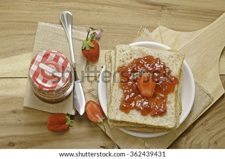 Strawberry preserve or marmalade with bread on wood  - stock photo
