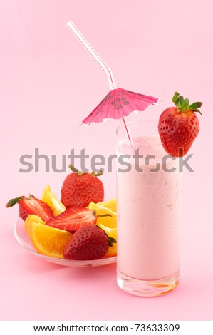 Strawberry protein cocktail with decoration and fruits on pink background.