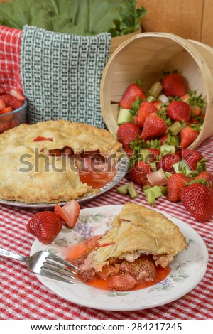 Strawberry-Rhubarb Pie on plate on a country table with strawberries and rhubard and a red and white checkered table cloth - stock photo