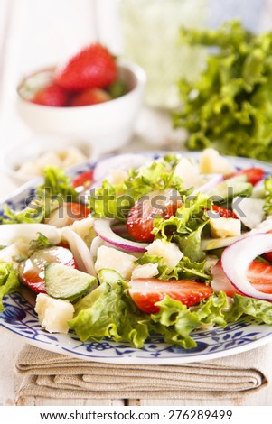 Strawberry salad with cucumber, red onion and parmesan cheese - stock photo