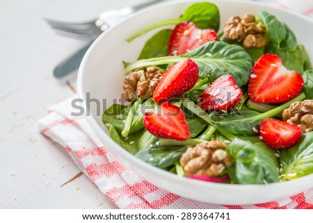 Strawberry salad with spinach, nuts, cheese in white bowl, plaid napkin, white wood background, closeup - stock photo
