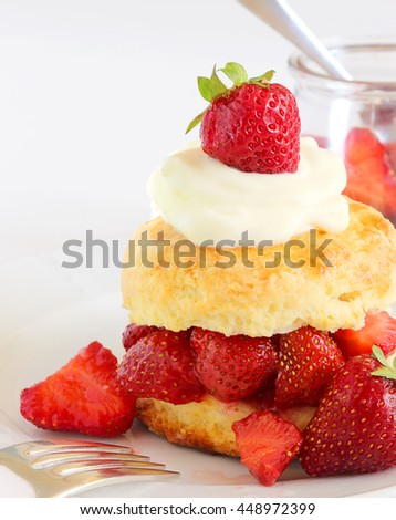 Strawberry shortcake topped with a dollop of whipped cream - stock photo