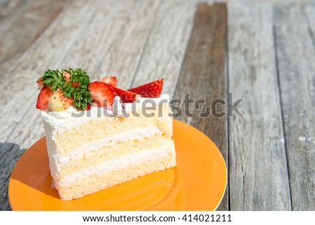 strawberry shot cake in orange dish on wooden table - stock photo