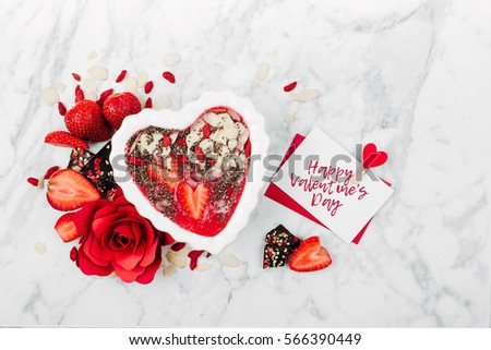 Strawberry smoothie in a bowl in the shape of a heart and valentine  card. Healthy and tasty breakfast on marble background