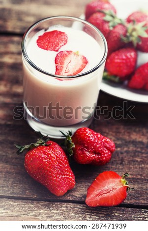 Strawberry smoothie in glass jar, over old wood table. - stock photo