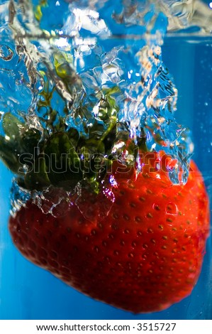 Strawberry Splash: A strawberry plunged into cool refreshing water. - stock photo