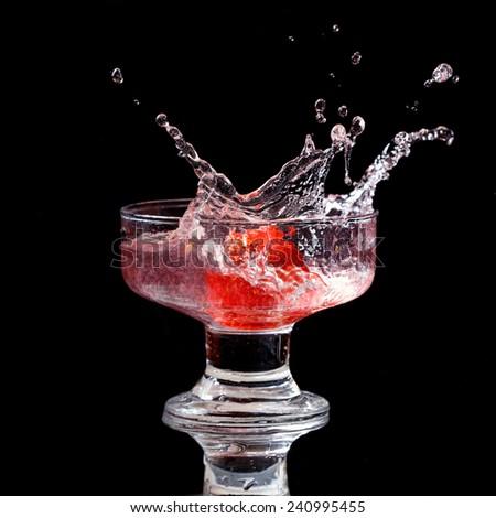 Strawberry splash isolated on black background - stock photo