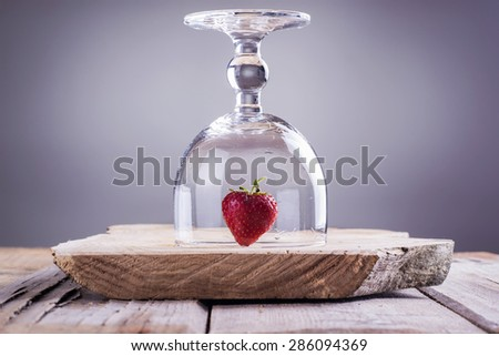 Strawberry standing on a wooden cutting board under a wine glass - stock photo