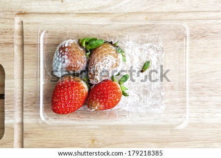Strawberry with fungi in plastic box on Chopping wood. - stock photo