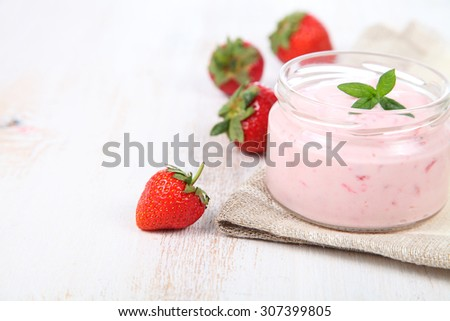 Strawberry yogurt and ripe strawberry on a wooden table. Summer dessert.