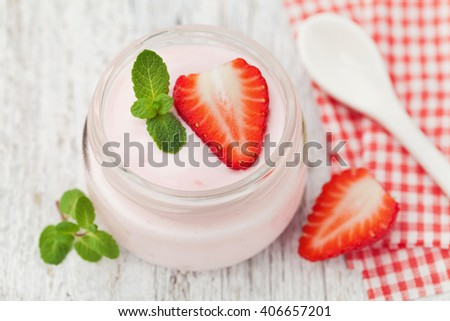 Strawberry yogurt decorated mint leaves in glass jar on white rustic table, diet breakfast