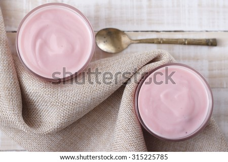 strawberry yogurt in glass with vintage spoon and cloth place on white wooden background. pink yogurt. pink yoghurt, strawberry yoghurt. - stock photo
