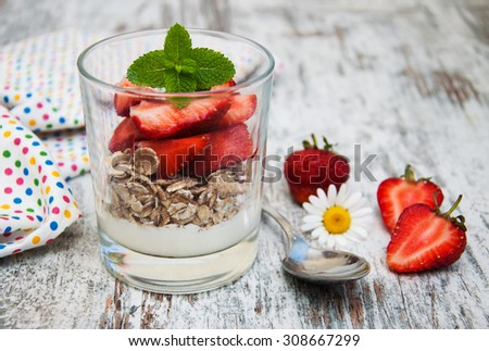 strawberry yogurt with muesli on a old wooden background - stock photo