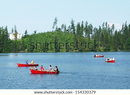 STRBSKE PLESO, SLOVAKIA - JULY 7: People sail in boats in mountain lake Strbske Pleso on July 7, 2012 in mountains High Tatras. Strbske Pleso is famous tourist destination in High Tatras.