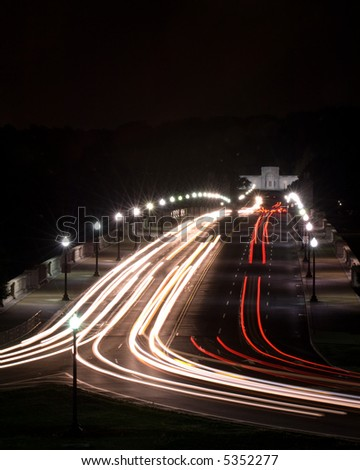 Streaks of automobile headlights and tail lights streak across a bridge in Washington, DC. - stock photo
