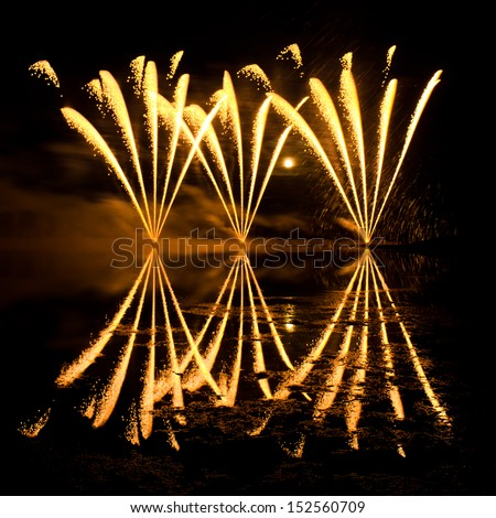 Streaks of Golden Fireworks reflected in a murky lake - stock photo
