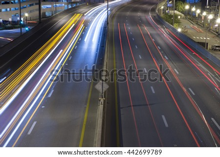 Streaks of headlights and taillights from highway traffic, overhead view.