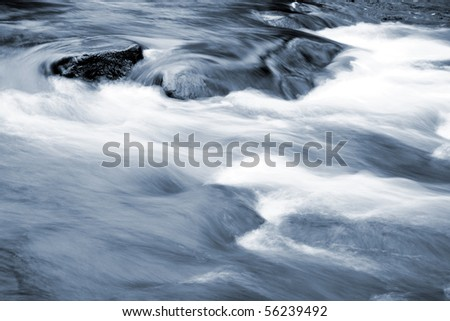 Stream flowing in over rocks. - stock photo