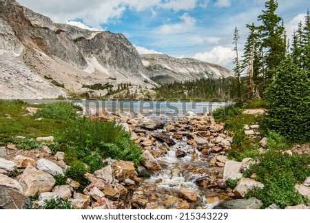 Stream from a Mountain Lake:  A small stream carries overflowing water from a mountain lake in southern Wyoming.  - stock photo