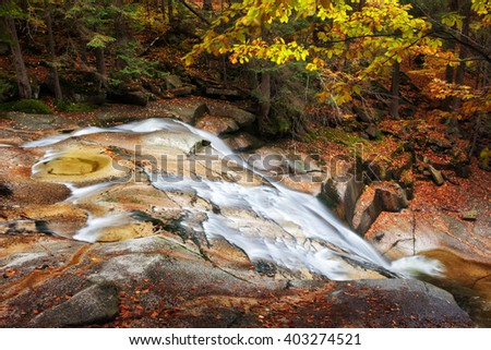 Stream in autumn mountain forest, picturesque, tranquil scenery in Sudetes, Czech Republic - stock photo