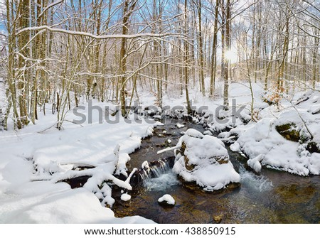 stream in the wood in winter with snow and ice - stock photo