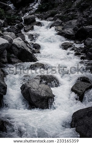 Stream of mountain river. Black-white - stock photo