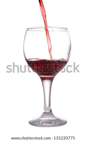 Stream of red wine flows in a wineglass, isolated on white - stock photo