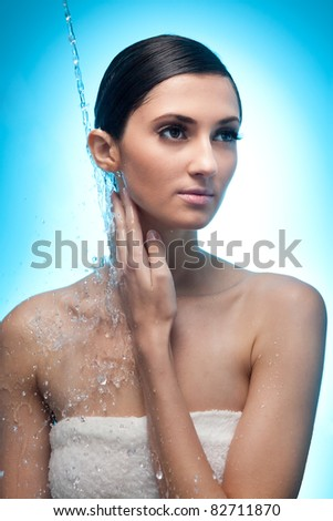 stream of water falling on the young woman with beautiful skin - blue background - stock photo