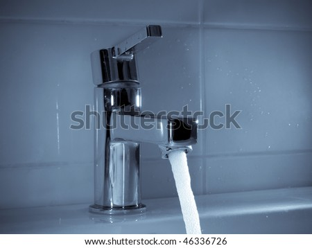 Stream of water flowing from faucet in bathroom - stock photo