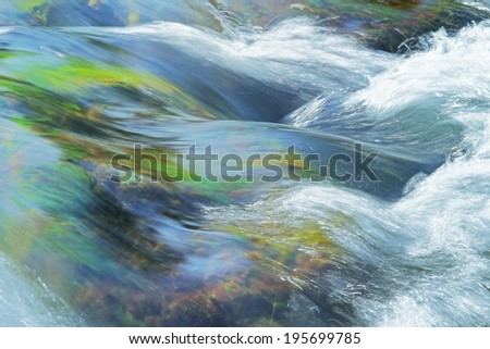 stream rapids in a river, smooth water surface with splashes - stock photo