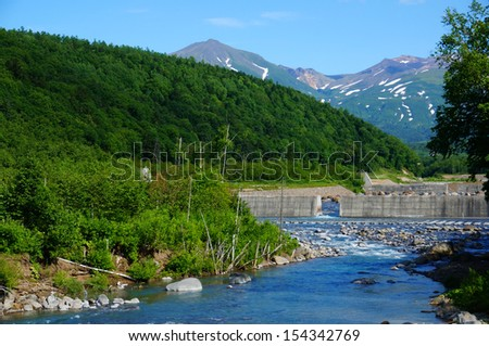 Stream, small dam and mountain, north of Japan - stock photo