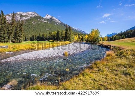 Stream with a pebbly bottom flows among the mountains. Magnificent picturesque valley in Banff National Park - stock photo