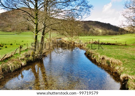 Stream with reflections of trees running through green fields in the lush countryside of the English Lake District - stock photo