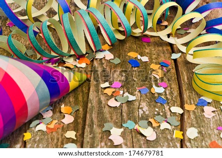 streamer, confetti, party hat on wood - stock photo