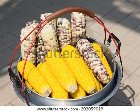 Streaming of corn in pot at outdoor marketplace. Thailand - stock photo