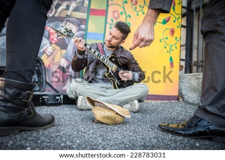 Street artist performing om the streets - People listening man playing guitar and giving charity - stock photo