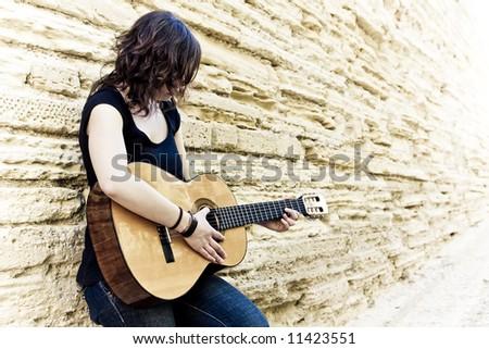 Street artist playin guitar on the wall - stock photo