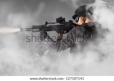 Street Assault, riot police firing his submachine gun, smoke - stock photo