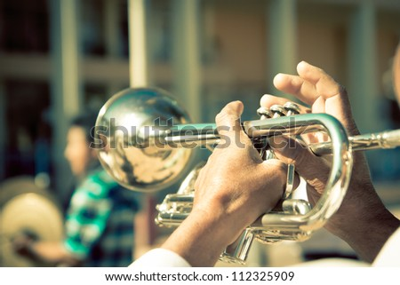 street band playing, selective focus on the hands with trumpet - stock photo