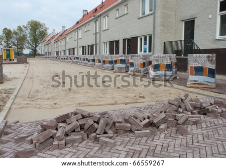 street being paved in front of some newly built terraced houses - stock photo