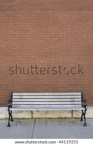 street bench in front of red brick wall - stock photo