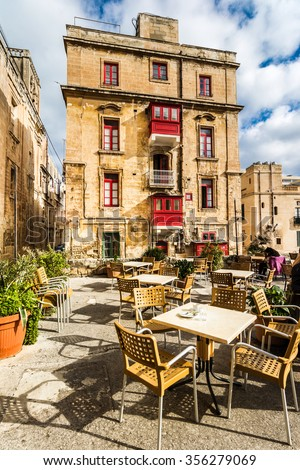 Street cafe in Malta outdoor with tables and chairs and beautiful building behind