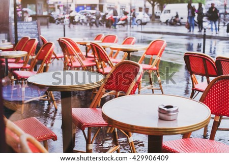 street cafe in Paris in rainy day, red wicker chairs and tables - stock photo