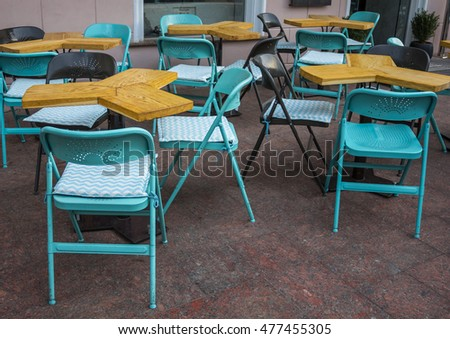 street cafe in summer with blue chairs and wooden tables