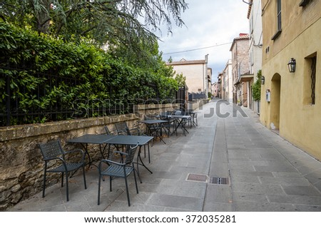 Street cafe tables abandoned  in medieval town in Umbria, Italy - stock photo